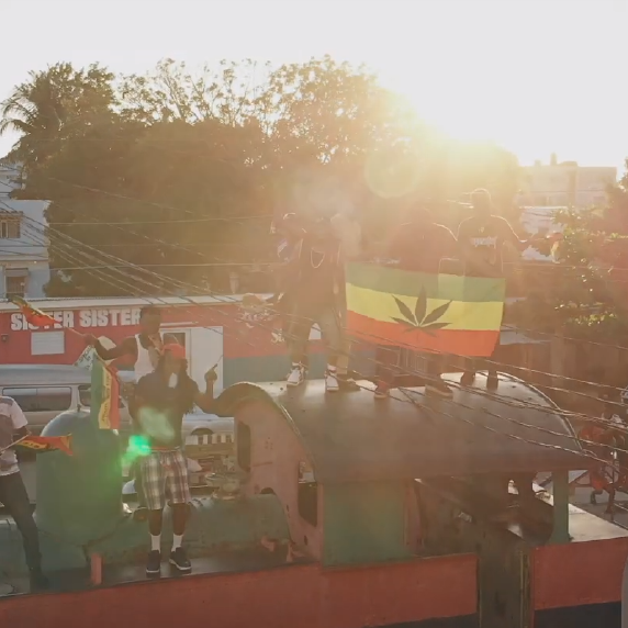 Jahman music video screen shot from Herbs, musicians dancing on bus in Jamaica