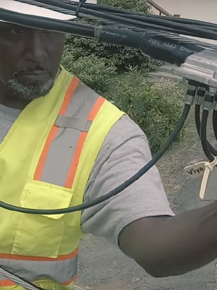 screen shot from documentary for Viya, Virgin Islands, worker fixing telephone lines on pole