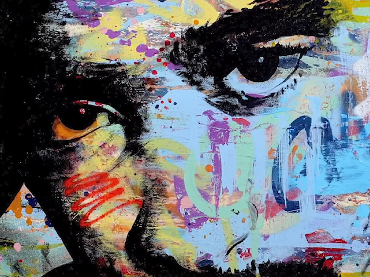 Screen shot from Nyorah music video Profit and Hustle, graffiti portrait of artist face, colorful